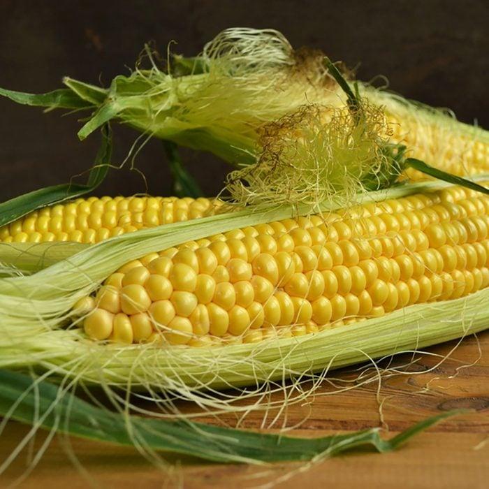 Three fresh corn cob on wooden table