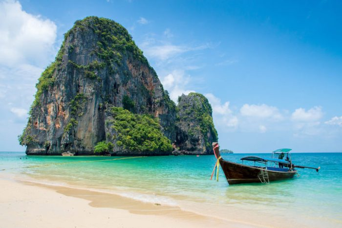 Nice beach and turquoise water with the limestone island and a small boat besides at Krabi Thailand