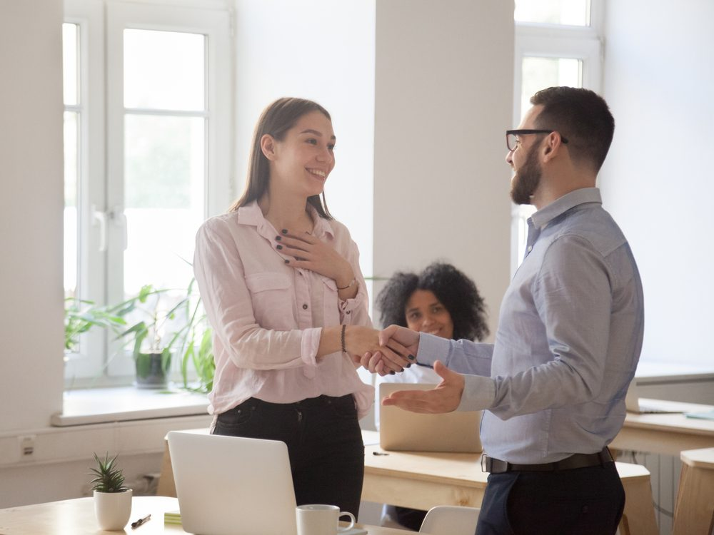 Male boss congratulating female employee