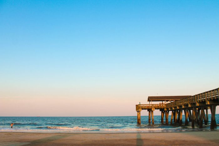 tybee island boardwalk and pier at sunset with waves crashing, bright bold colors in the sky