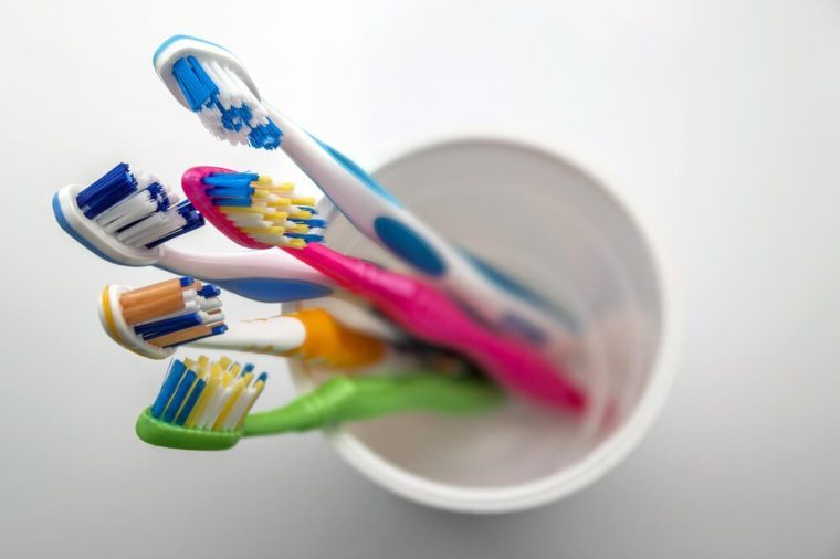 Close up shot of set of multicolored toothbrushes in glass on clean toilet on white background, concept dental.