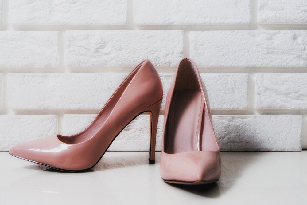 High heels. Beige high heels with a mascara on a white, brick background. The concept of fashion, modernity. Female high heels lie on white floor, two high heels.
