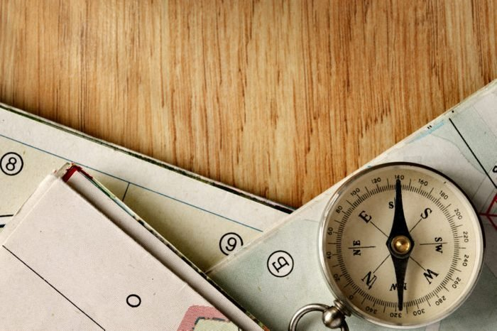 Close up Vintage Compass Instrument on Top of a Wooden Table with Folded Maps, Captured in High Angle View.