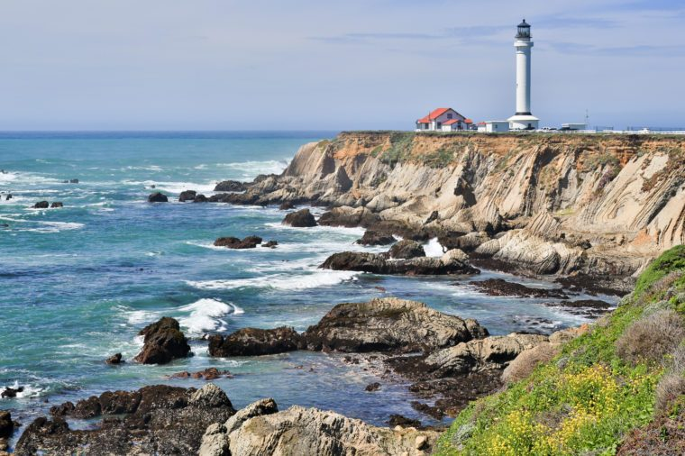 Point Arena Lighthouse and rocky coastline of the Pacific Ocean. Mendocino County, California, USA.