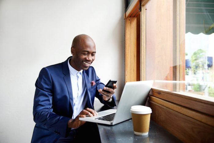 Portrait of happy african businessman using phone while working on laptop in a restaurant