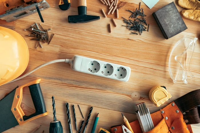 Power strip extension cord on carpentry woodwork woodwork desk, top view
