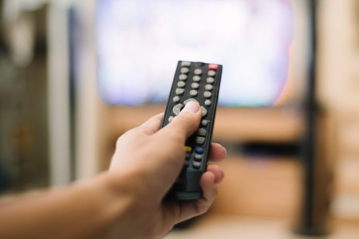 Hand holding use remote control and watching television at home.