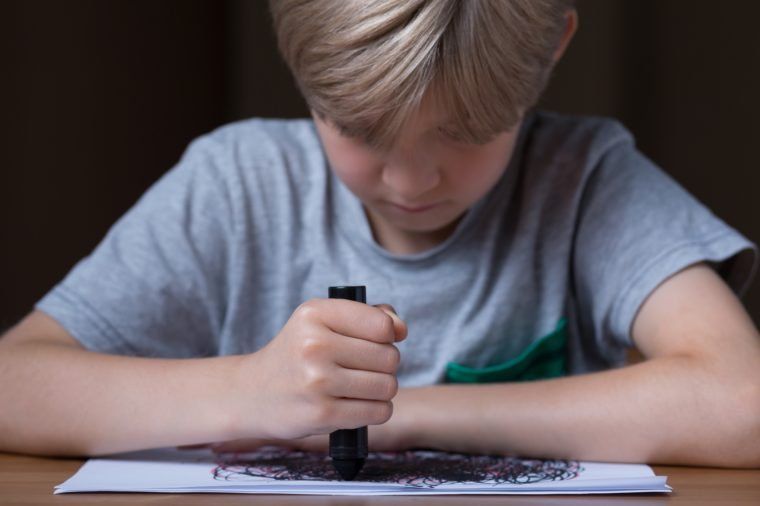 Young boy is drawing during his therapy