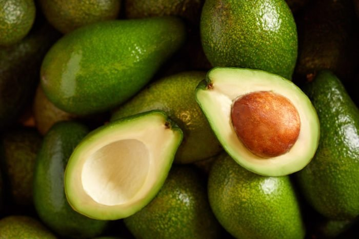 Bunch of green Avocados. One of them is opened that the stone and the pulp are visible
