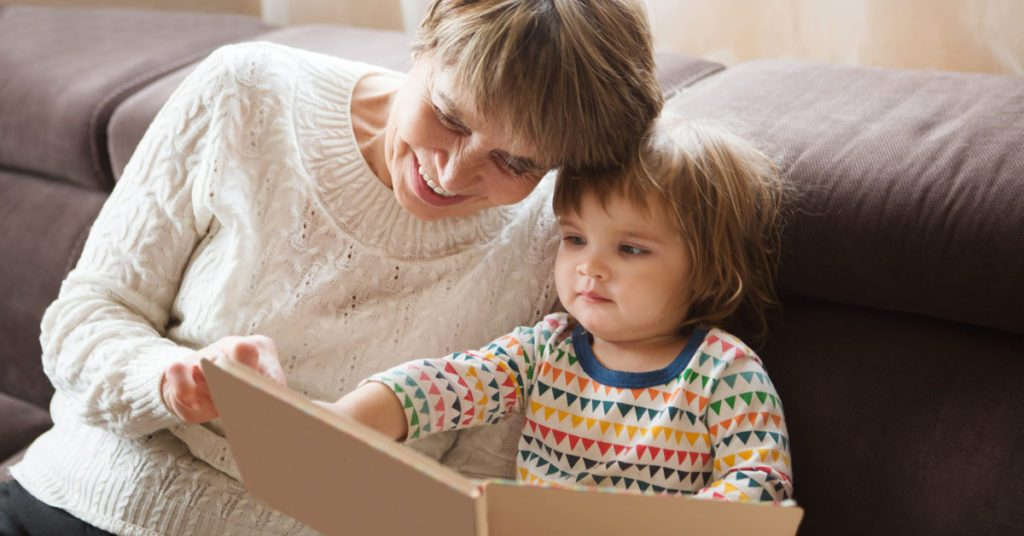 Senior woman reading book to young baby