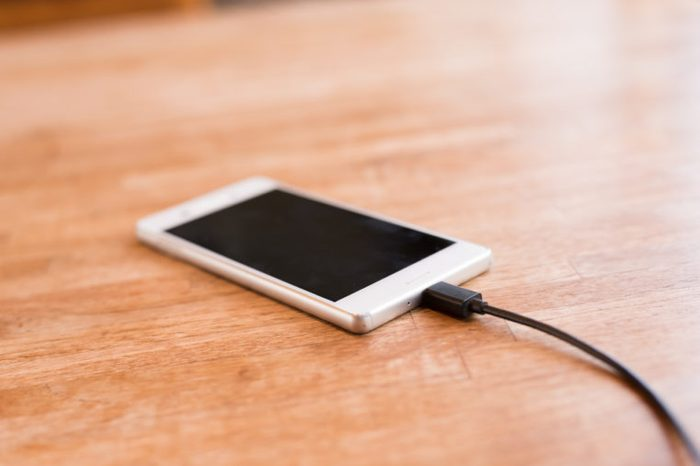Mobile smart phone charging on wooden desk