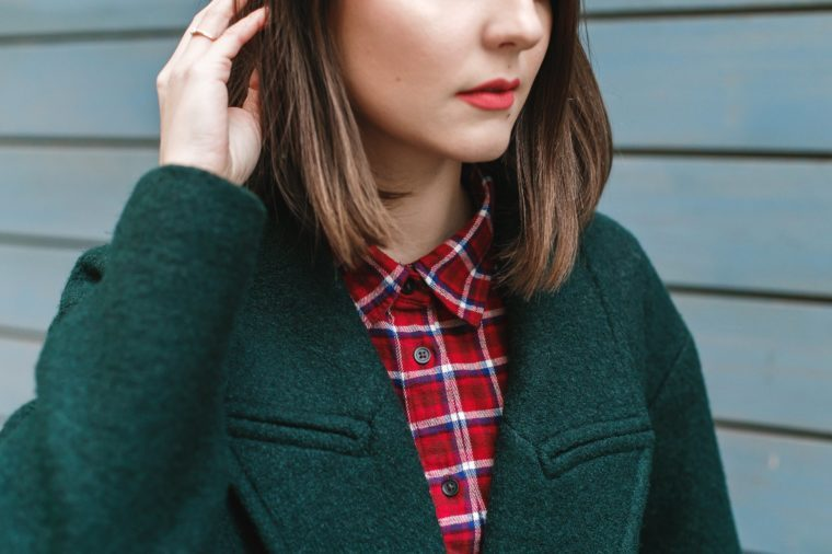 Young brunette woman with stylish short haircut wearing red plaid shirt and green coat standing near blue wooden wall on the city street. Trendy casual outfit. Details of everyday look. Street fashion