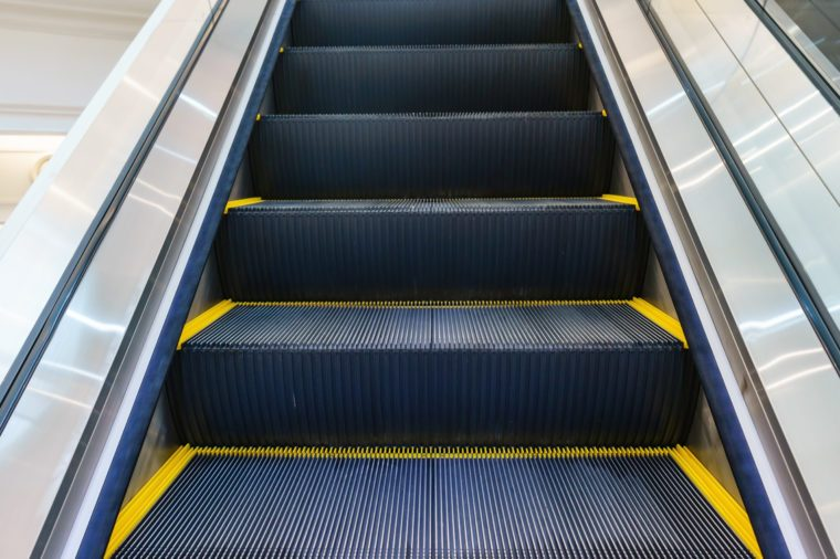 Escalator in Community Mall, Shopping Center. Moving up staircase. electric escalator. Close up to escalators. Close up floor platform. yellow bands. metal line steel. yellow gray steel line.