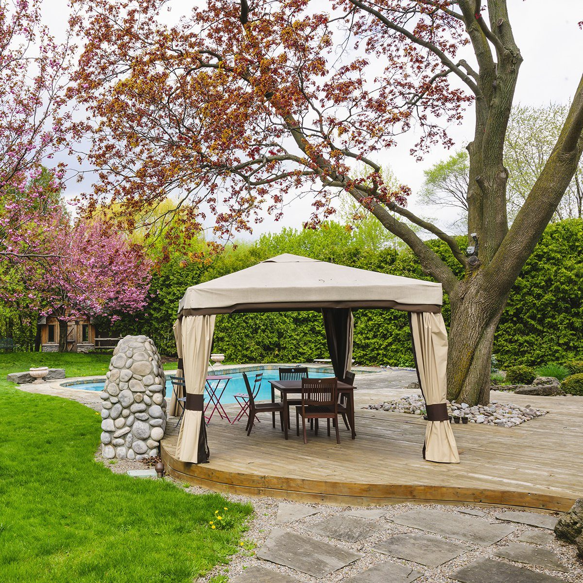 Residential backyard with gazebo, deck, stone patio and swimming pool