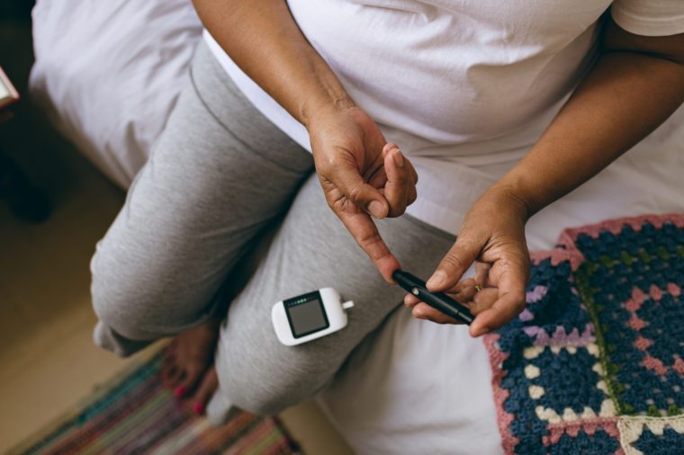 Low section of mixed race female senior patient checking blood sugar level with glucometer at retirement home
