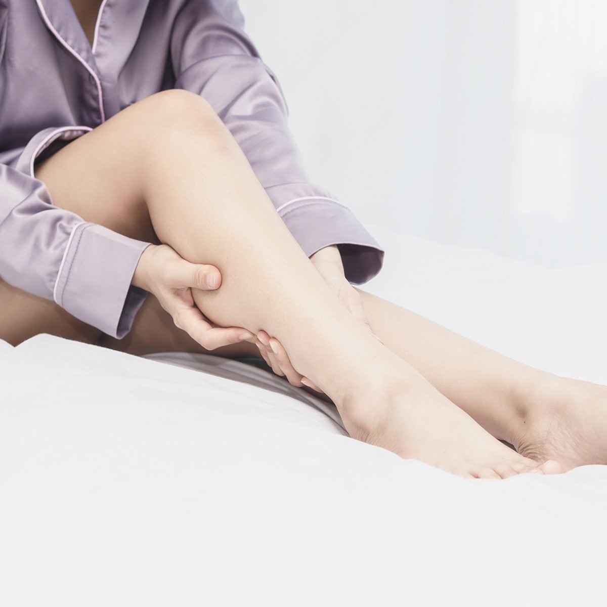 women lag pain on bed in bed room in the morning.color tone