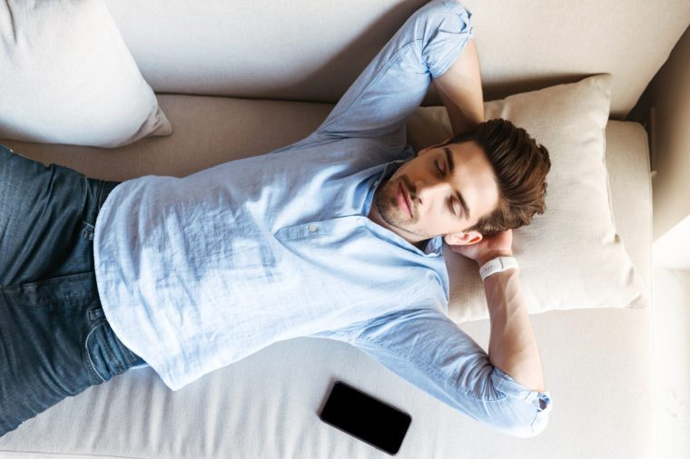 Top view of a young man sleeping on the couch at home with mobile phone