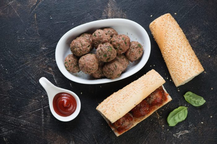 Baked beef meatballs and homemade sub sandwiches. Flat-lay on a dark brown stone surface