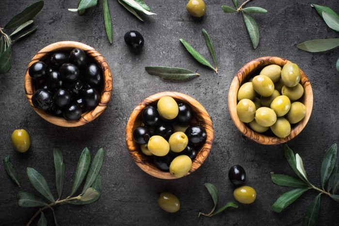 Black and green olives in wooden bowls. Top view on black background.