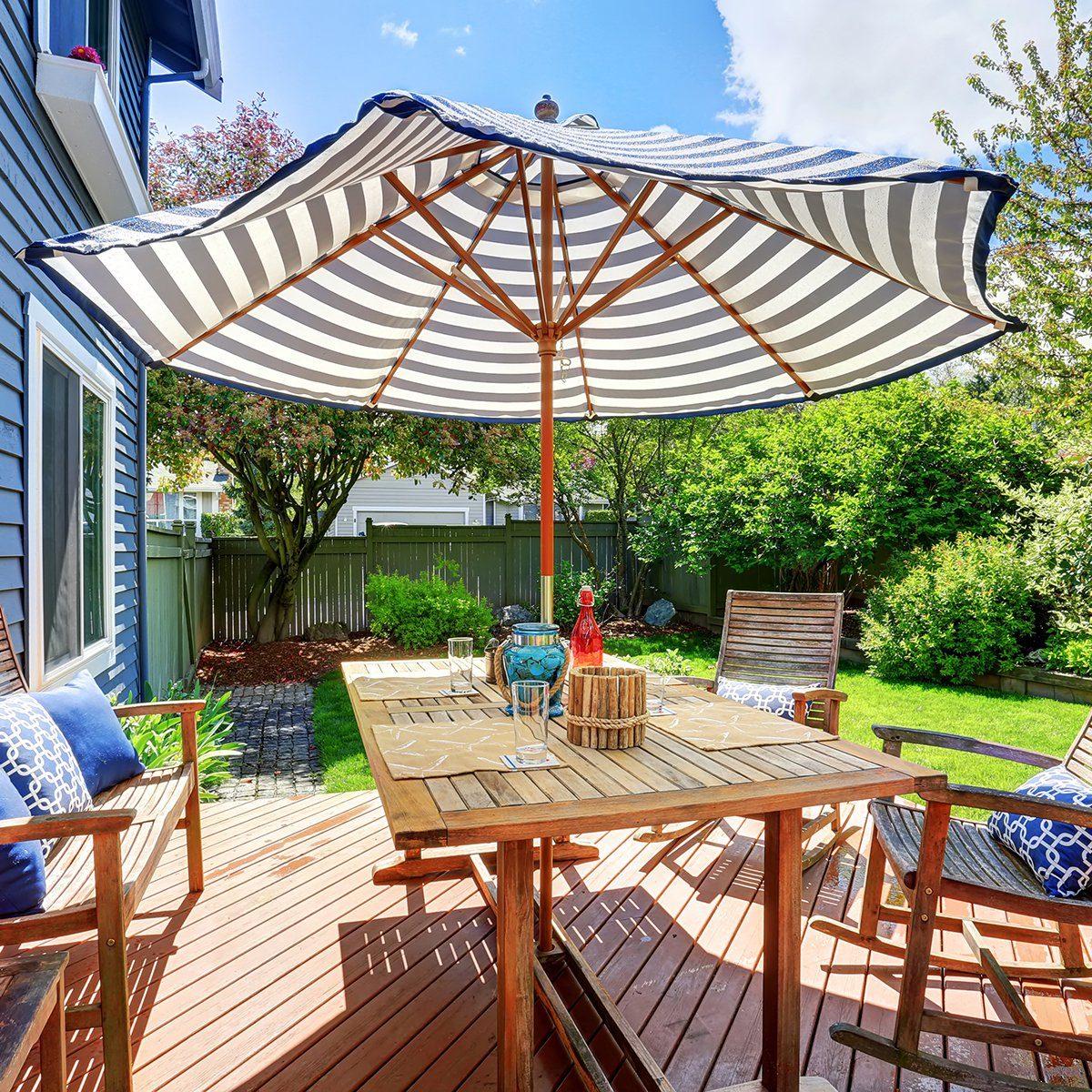 Wooden walkout deck in the backyard garden of blue siding house.
