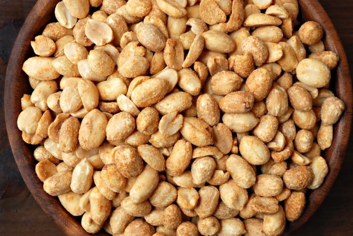 Delicious roasted peanuts in wooden bowl with wood background. Viewed from above.