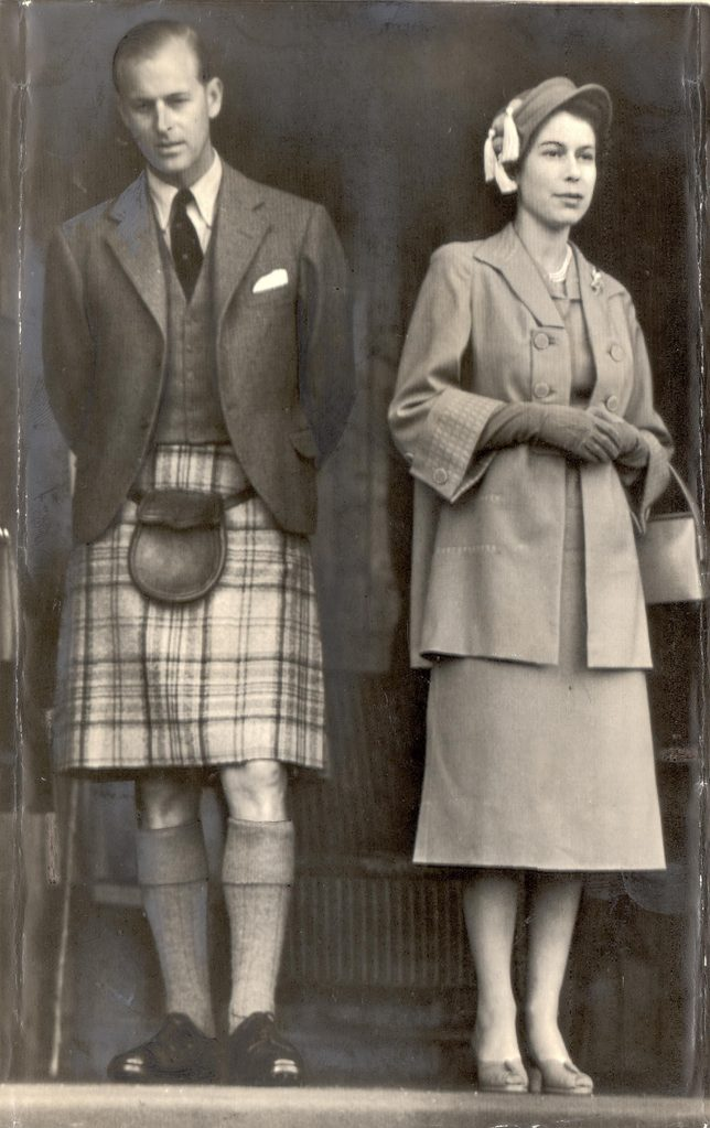 Queen Elizabeth & Duke Of Edinburgh - September 1952 Wearing Kilts - Duke Wears Balmoral Tartan .... The Queen Is In Grey And Her Hat Is Trimmed With Yellow Tassels; The Duke Of Edinburgh Wears The Mauve And Grey Balmoral Tartan. They Are Watching Th