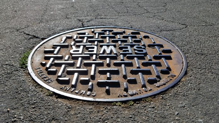 Sewer metal cap/cover on the road under shade in close up