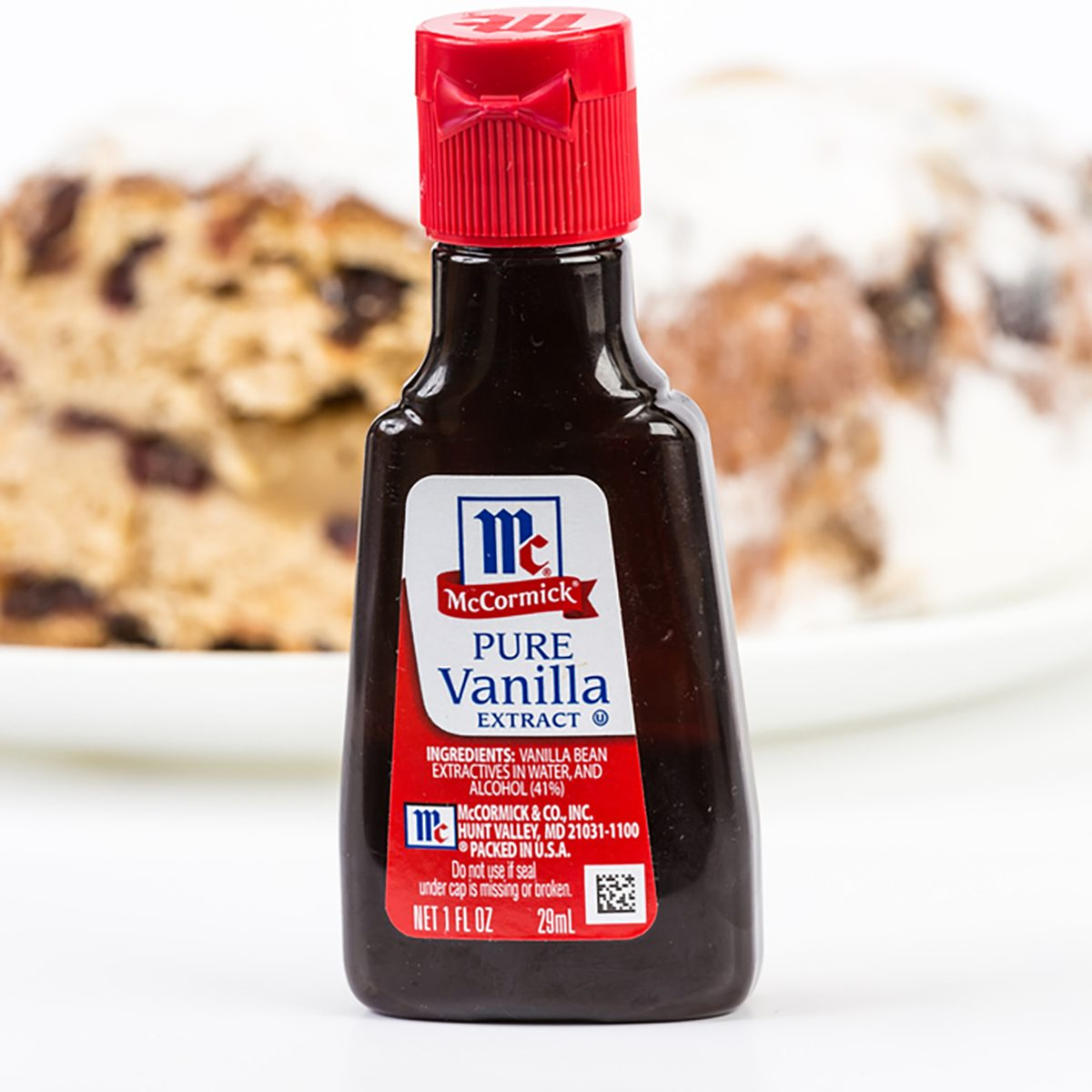 Small bottle of McCormick Pure Vanilla Extract with baked cake in background. Horizontal with copy space.