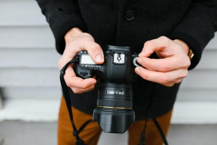 A professional photographer adjusts the camera before shooting, hands, camera, background