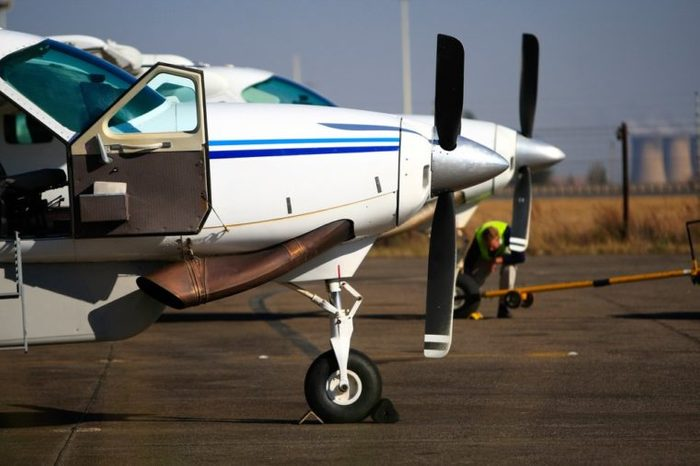Two light aircraft standing next to each other on the runway