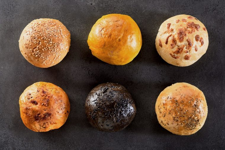 High Angle View of Variety of Six Hamburger Buns or Dinner Rolls Arranged in Two Rows on Textured Table or Counter Surface