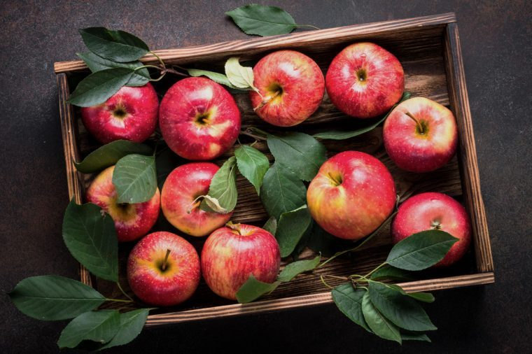 Red apples in wooden tray on dark stone table. Top view.