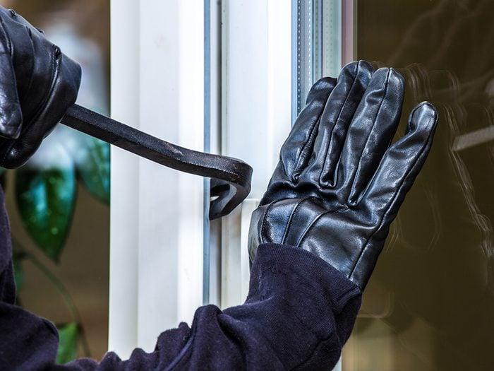 Sneaky ways burglars break in - burglar with crowbar at window
