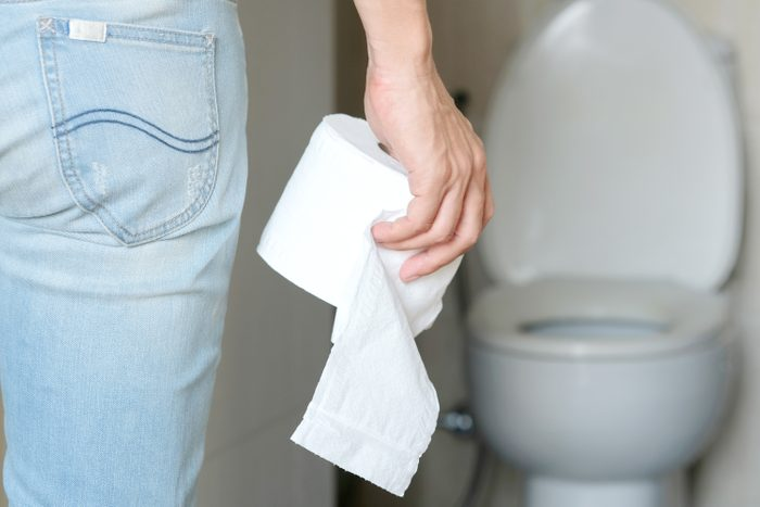 Man's hand, he holds a roll of toilet paper Going to the bathroom Toilet toilet background