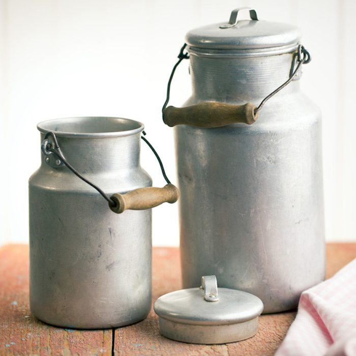 vintage milk cans on old wooden table; Shutterstock ID 181187597