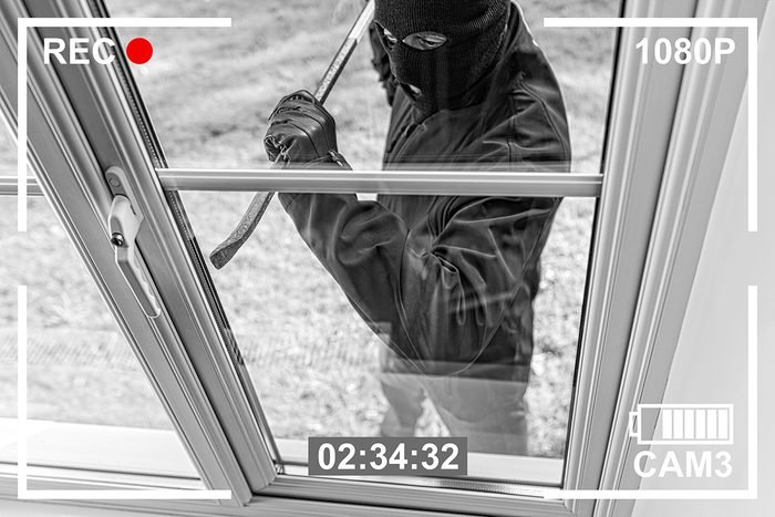 Ways burglars break in - burglar opening window with crowbar