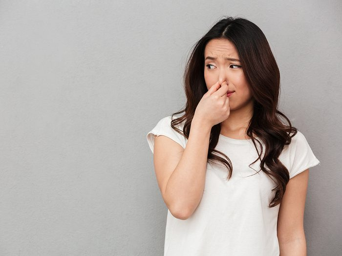 What your poop says about your health - woman reacting to bad smell