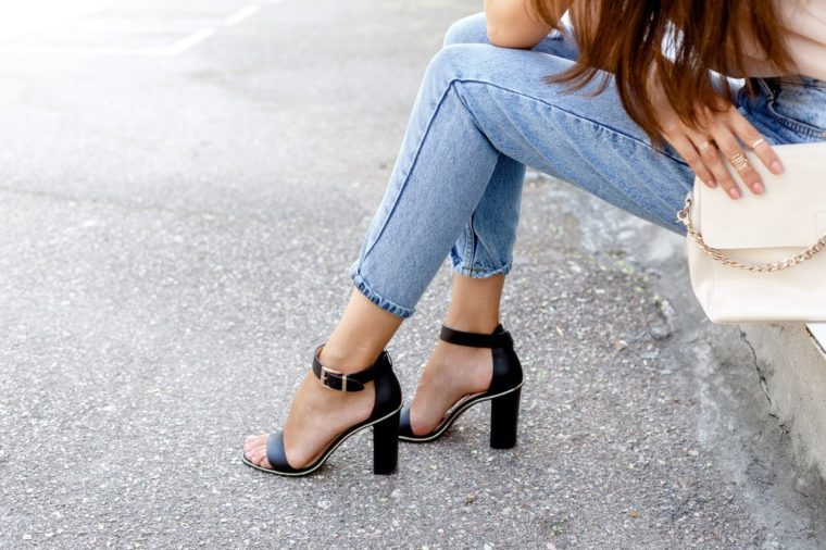 Women's legs in blue cropped denim jeans and black high heel sandals in the city street. Trendy elegant casual outfit. Details of everyday summer look. Street fashion.