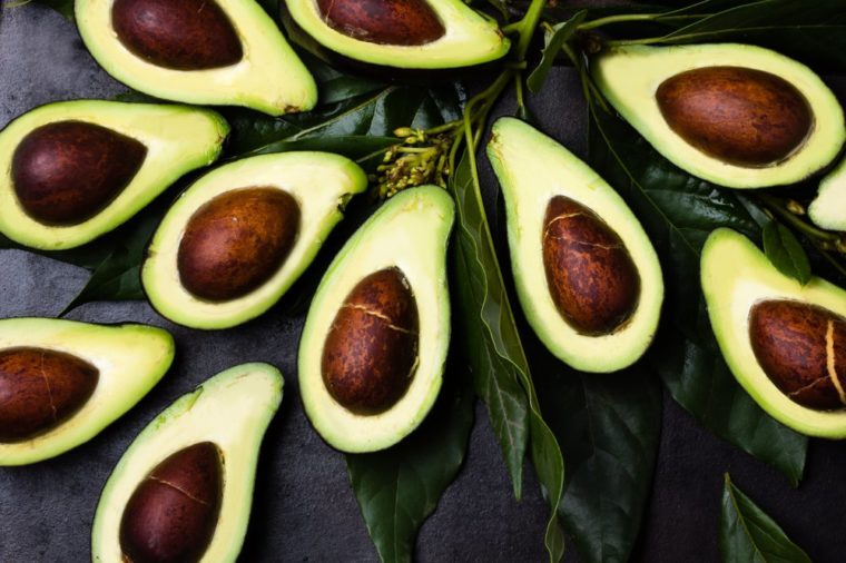 Avocado. Fresh avocado palta with leaves on black background. Guacamole ingredient. Vegetarian or healthy eating. Healthy fat