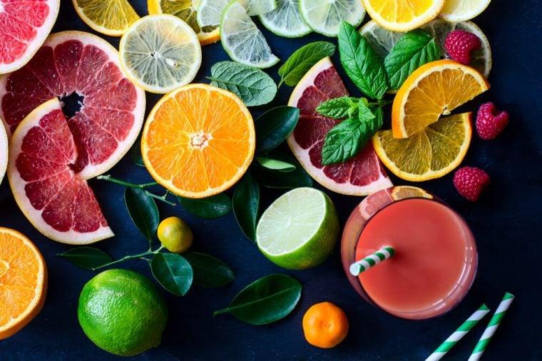 Citrus juice and slices of orange, grapefruit, lemon. Vitamin C. Black background