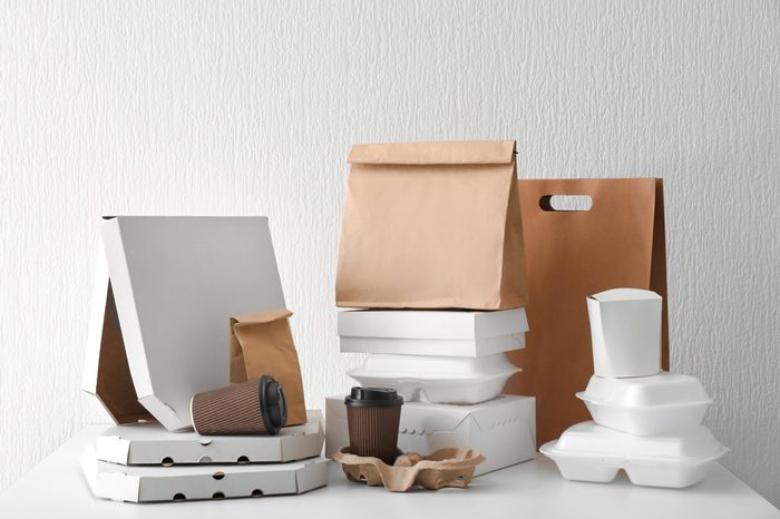 Assortment of food delivery containers on white table