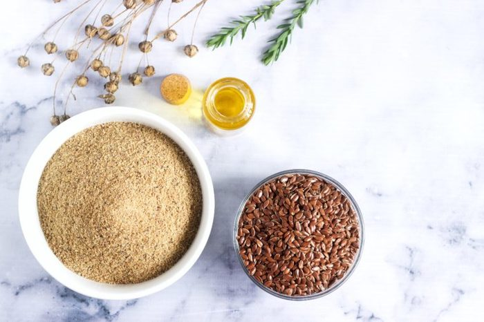 Flax seeds, flax flour, oil with sprouts and flax seed boxes on a light background.