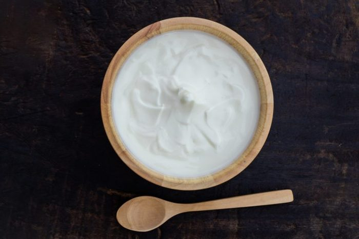 Greek yogurt or sour cream in a wooden bowl on dark table top view. Healthy food nutrition.