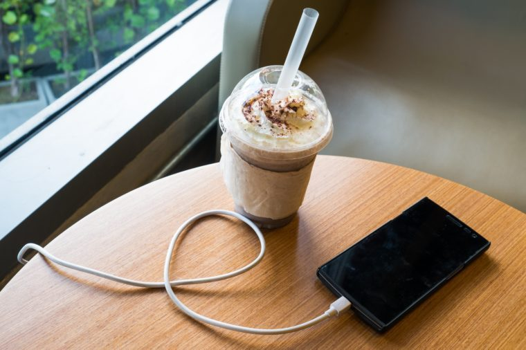 cell phone charging in the cafe with a plastic cup of iced chocolate frappe