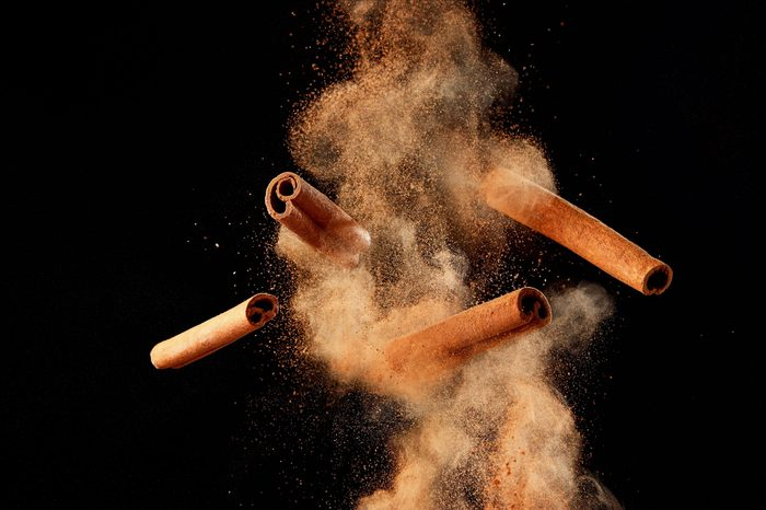 Food explosion with cinnamon sticks and powder, on black background.