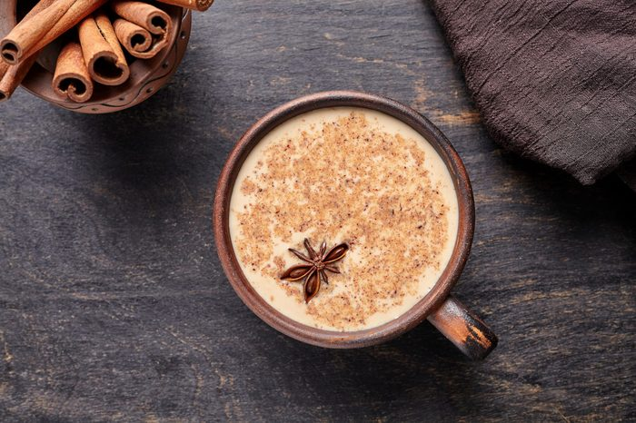 Masala tea chai latte traditional warm Indian sweet milk spiced drink, ginger, cinammon sticks, fresh spices blend organic infusion healthy wellness beverage in rustic clay cup on dark table