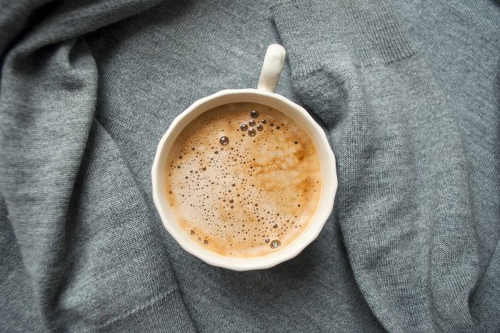 A cup of fresh coffee with beautiful foam on grey background. Flat lay style.