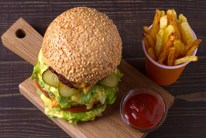 Homemade triple decker burger and fries on dark wooden background. View from above