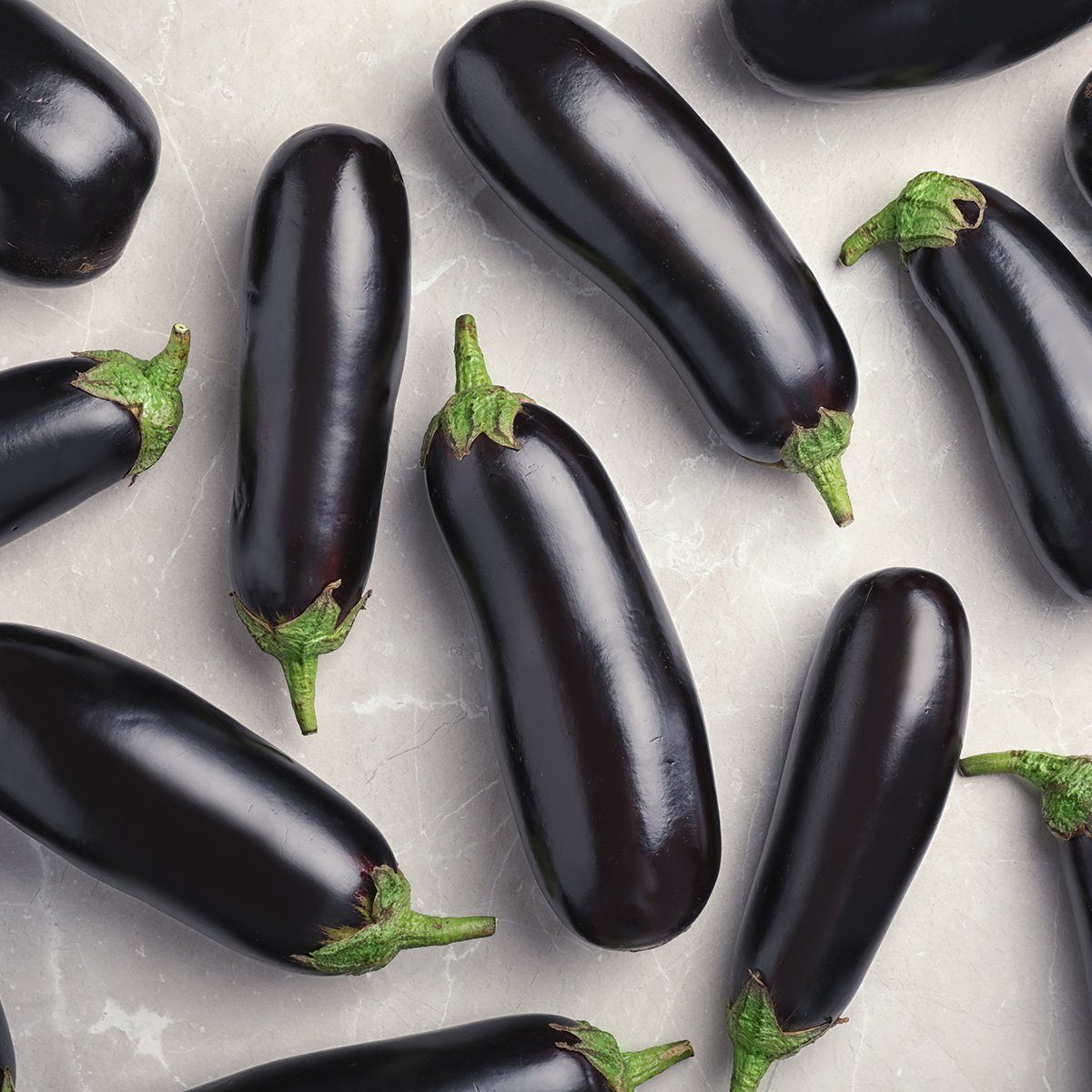Raw ripe eggplants on light background