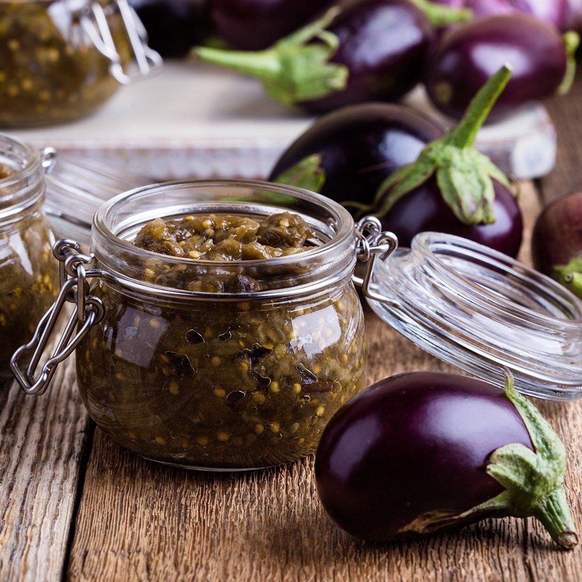 Eggplant preserves. Homemade vegetarian vegetable caviar in glass jar on rustic wooden table